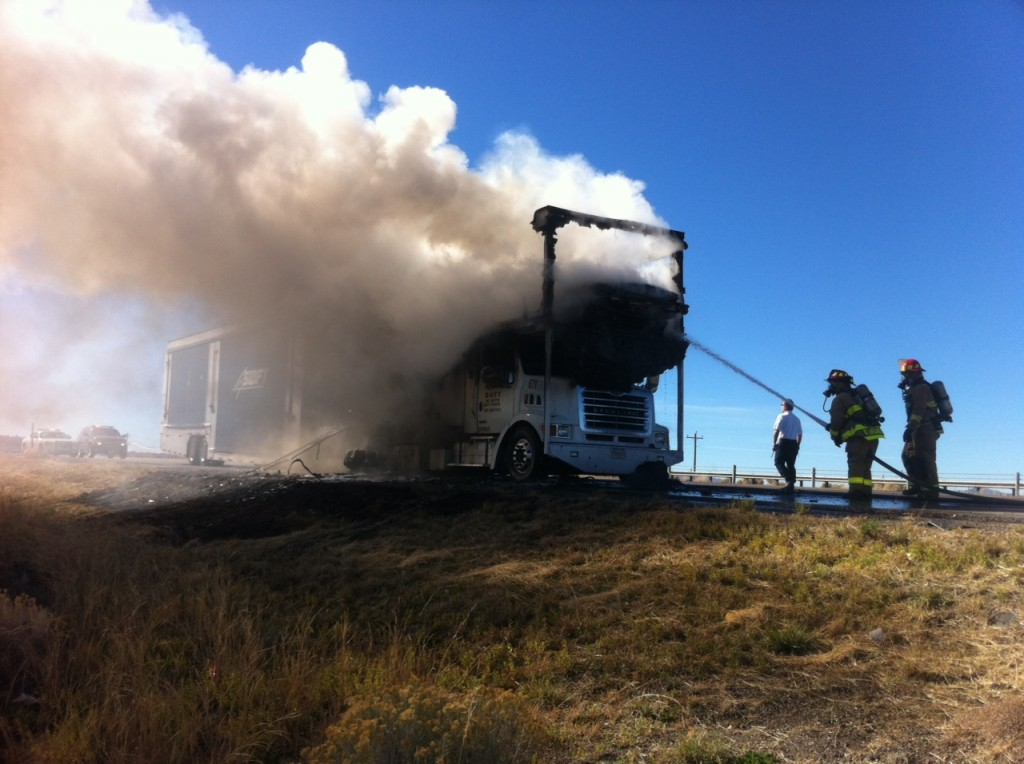 Fire fighters put out the burning auto transporter
